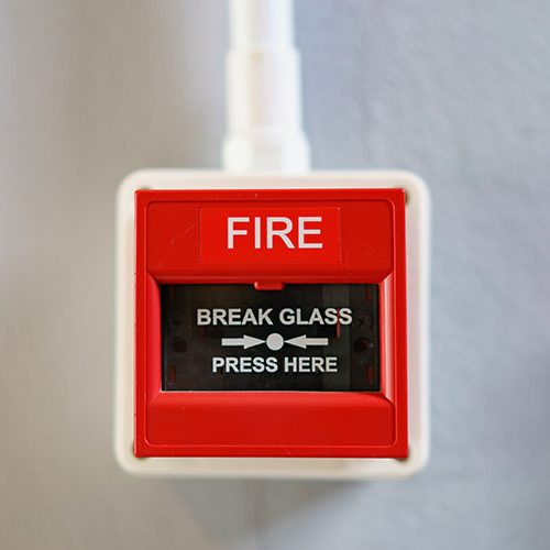 Red fire alarm box on white background.